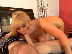 Experienced seductive mature golden-haired milf Karen Fisher with big juicy booty plus massive hanging hooters gives head to younger tattooed chap plus rides on his huge everlasting boner on bed