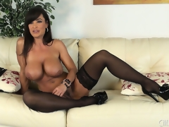 Lisa Ann positions seductively upon a pair of stockings and high heels